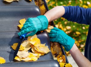 man wearing gloves cleaning gutters